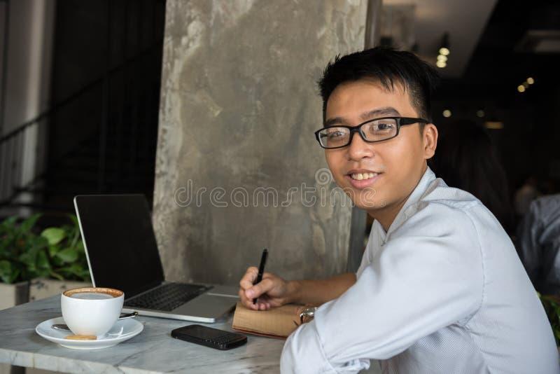 Sidosikt av att le asiatiska freelancerhandstilanmärkningar royaltyfri fotografi