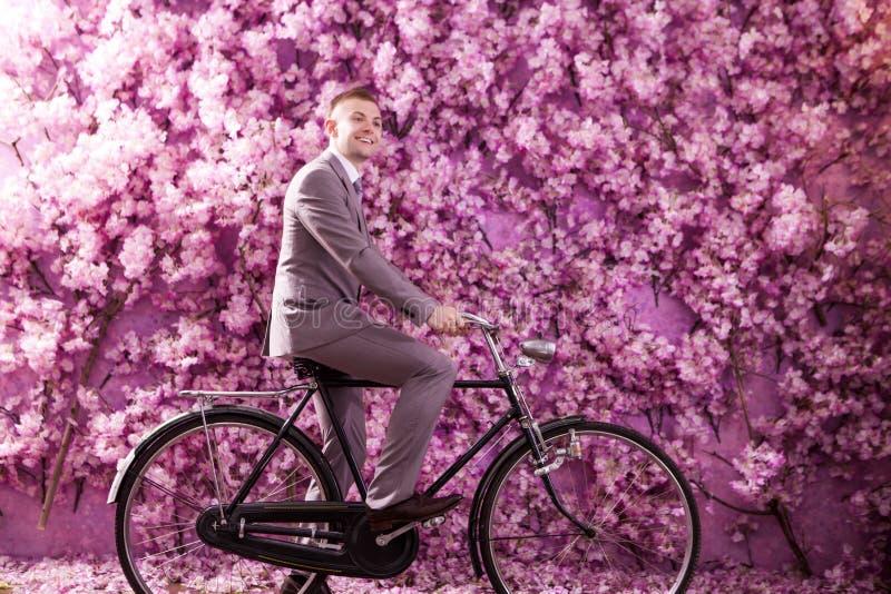 Download Sidosikt Av Att Le Brudgumridningcykeln Mot Väggen Som Täckas Med Rosa Blommor Fotografering för Bildbyråer - Bild av natur, full: 78732083