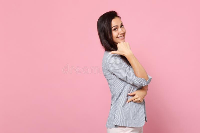 Sidosikt av att le den attraktiva unga kvinnan i randigt omslag som pekar tummen som isoleras åt sidan på den rosa pastellfärgade fotografering för bildbyråer
