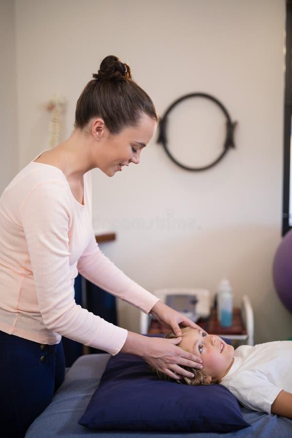 Sidosikt av att le den unga kvinnliga terapeuten som ger den head massagen till pojken som ligger på säng royaltyfria bilder