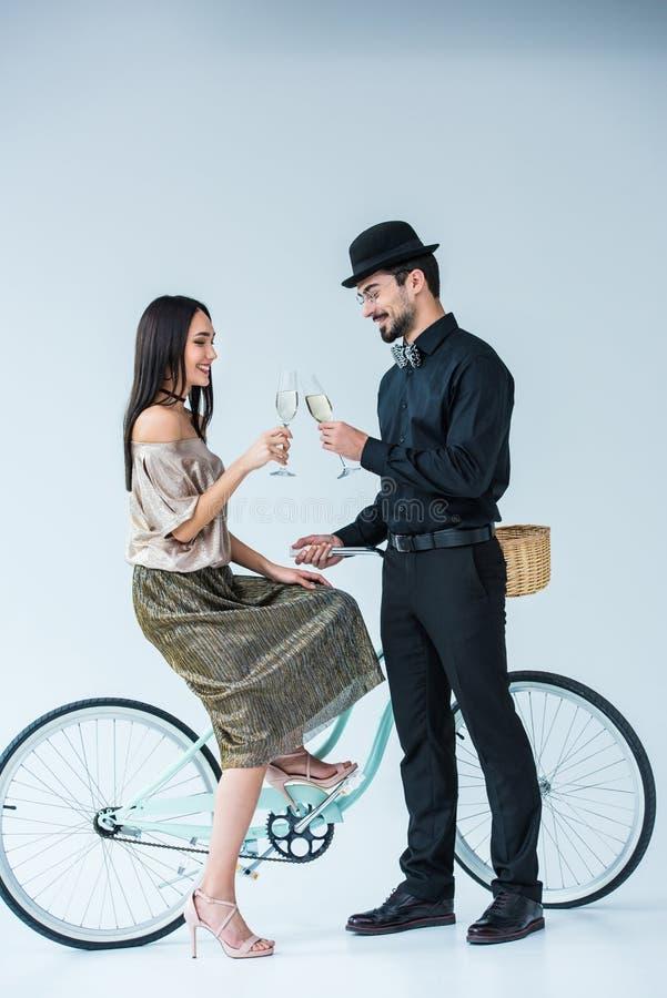 sidosikt av att le mångkulturella par med den retro cykeln som klirrar exponeringsglas av champagne fotografering för bildbyråer
