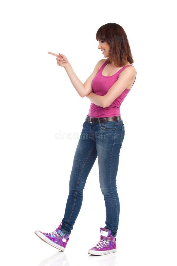 Sidosikt av att peka den skratta unga kvinnan fotografering för bildbyråer