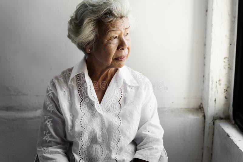 Sidosikt av den äldre asiatiska kvinnan med fundersamt framsidauttryck arkivbild
