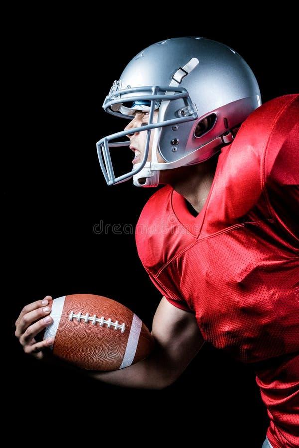 Sidosikt av den aggressiva idrottsmannen som spelar amerikansk fotboll royaltyfri fotografi