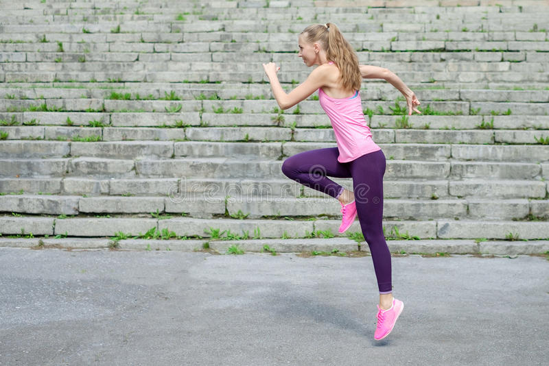 Sidosikt av den aktiva sportiga unga rinnande kvinnalöpareidrottsman nen med vikt för förlust för kondition för sport för kopieri royaltyfri fotografi