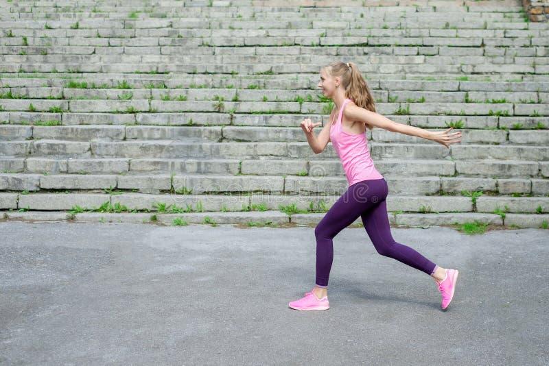 Sidosikt av den aktiva sportiga unga rinnande kvinnalöpareidrottsman nen med vikt för förlust för kondition för sport för kopieri fotografering för bildbyråer