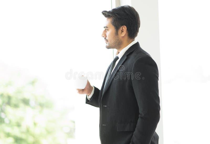 Sidosikt av den allvarliga eftert?nksamma chefen som har en kopp kaffe, medan se ut p? sikten till och med stora f?nster p? konto royaltyfri fotografi