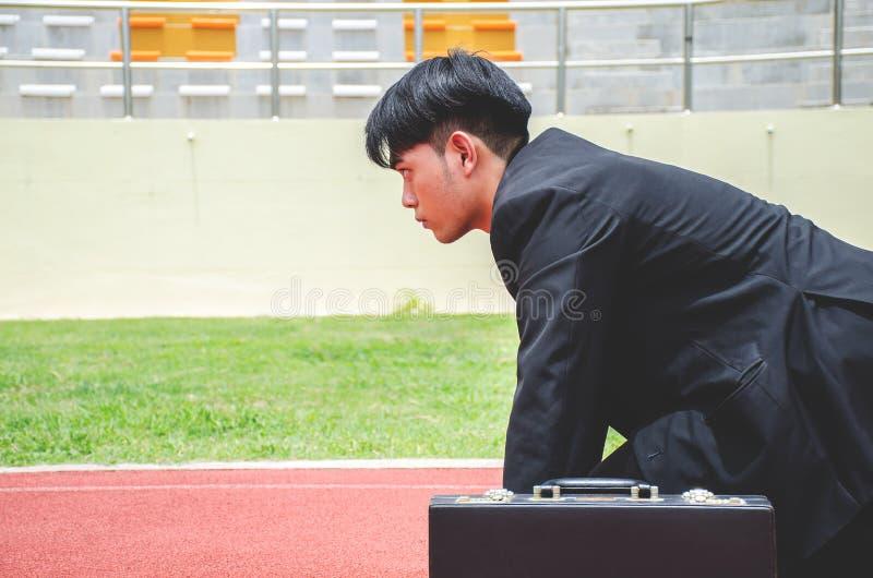 Sidosikt av den asiatiska affärsmannen som är klar att köra på gränderna av ett spår royaltyfri bild