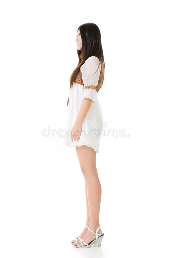 Sidosikt av den asiatiska kvinnan med den vita korta klänningen royaltyfri bild