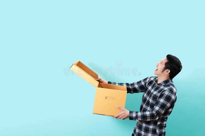 Sidosikt av den asiatiska mannen för lycklig kund som ler öppnings- och innehavasken som upp till ser kopieringsutrymme arkivfoton