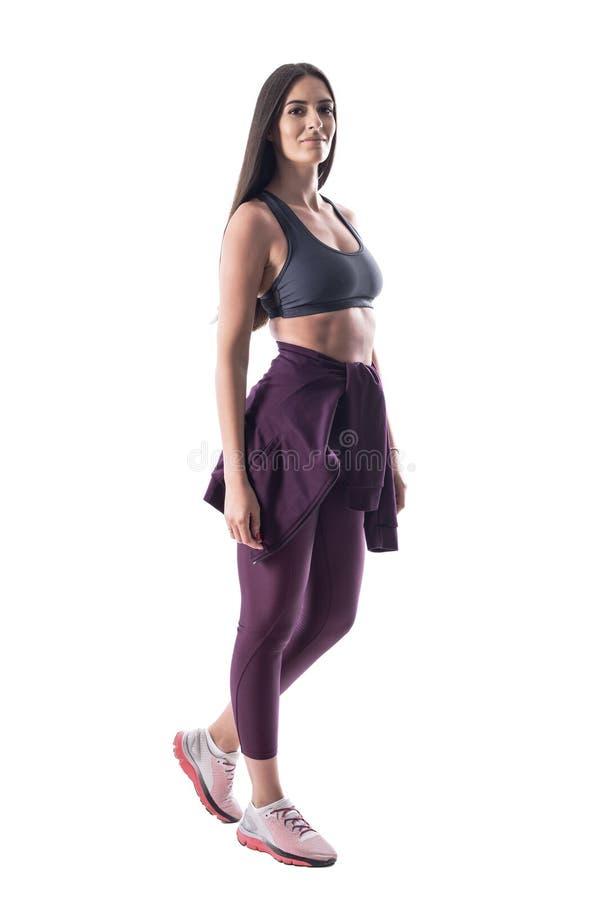 Sidosikt av den attraktiva kvinnliga konditionmodellen med stor abs, i att bekläda för sportar royaltyfri fotografi