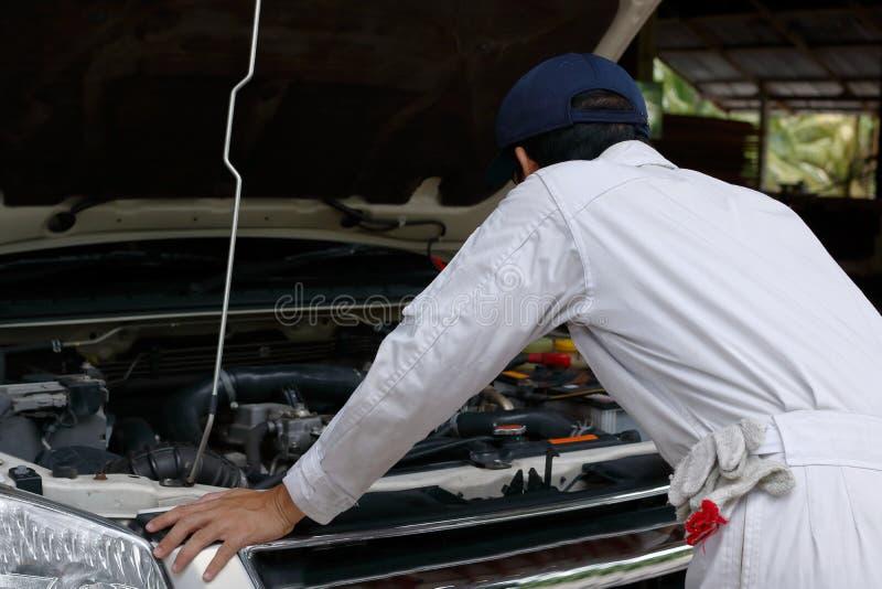 Sidosikt av den automatiska mekanikern i den vita enhetliga diagnostiserande motorn under huven av bilen på reparationsgaraget royaltyfri foto