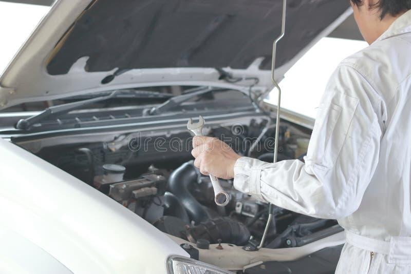 Sidosikt av den automatiska mekanikern i den vita likformign med skiftnyckeln som diagnostiserar motorn under huven av bilen på r royaltyfri fotografi