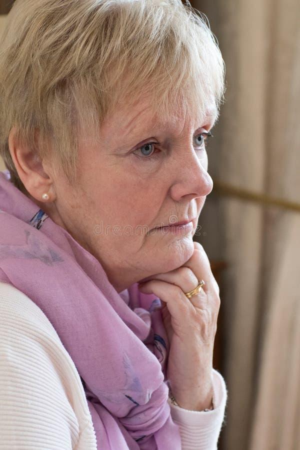 Sidosikt av den deprimerade höga kvinnan hemma royaltyfria bilder