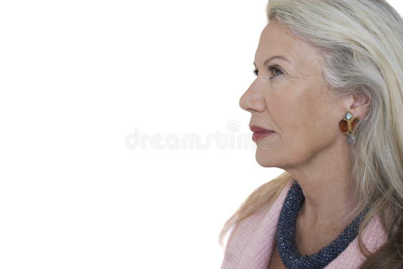 Sidosikt av den eftertänksamma höga kvinnan mot vit bakgrund fotografering för bildbyråer