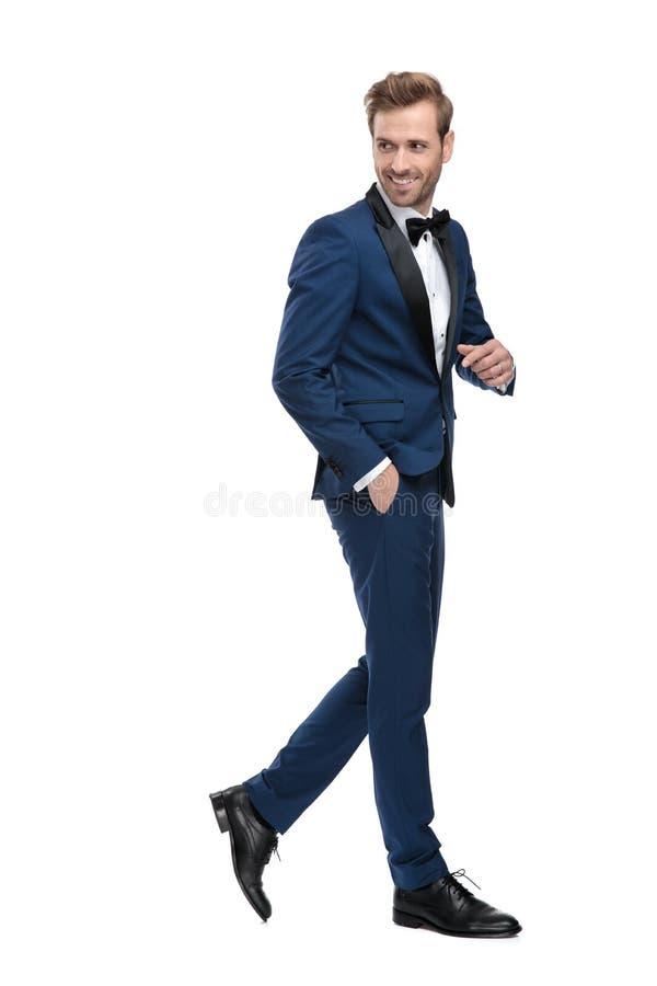 Sidosikt av den eleganta mannen som går, medan se tillbaka arkivfoton