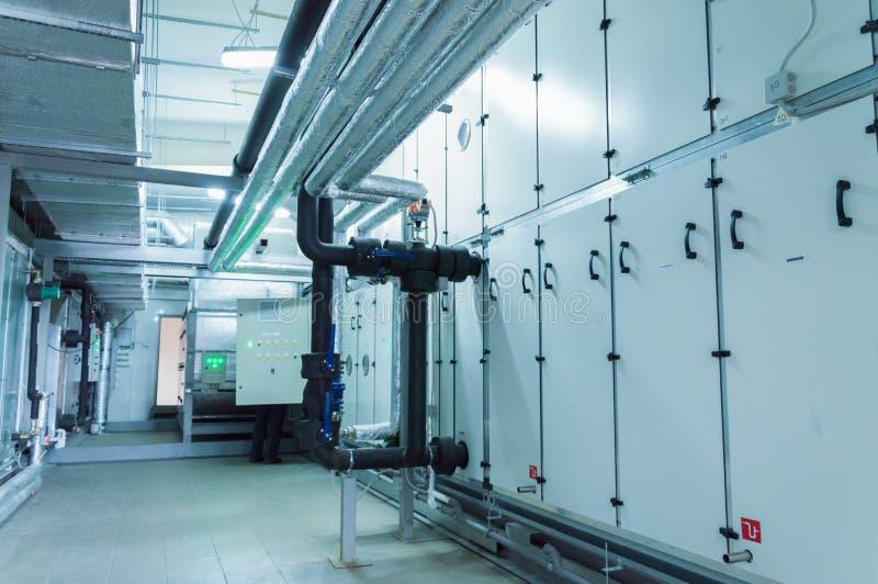 Sidosikt av den enorma gråa industriella luften som behandlar enheten i ventilationsväxtrummet arkivfoto