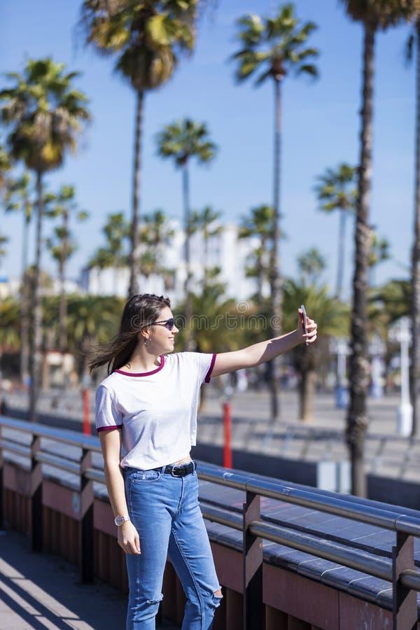 Sidosikt av den härliga le unga kvinnan som bär stads- kläder och solglasögon som står, medan ta en selfie utomhus i royaltyfria bilder