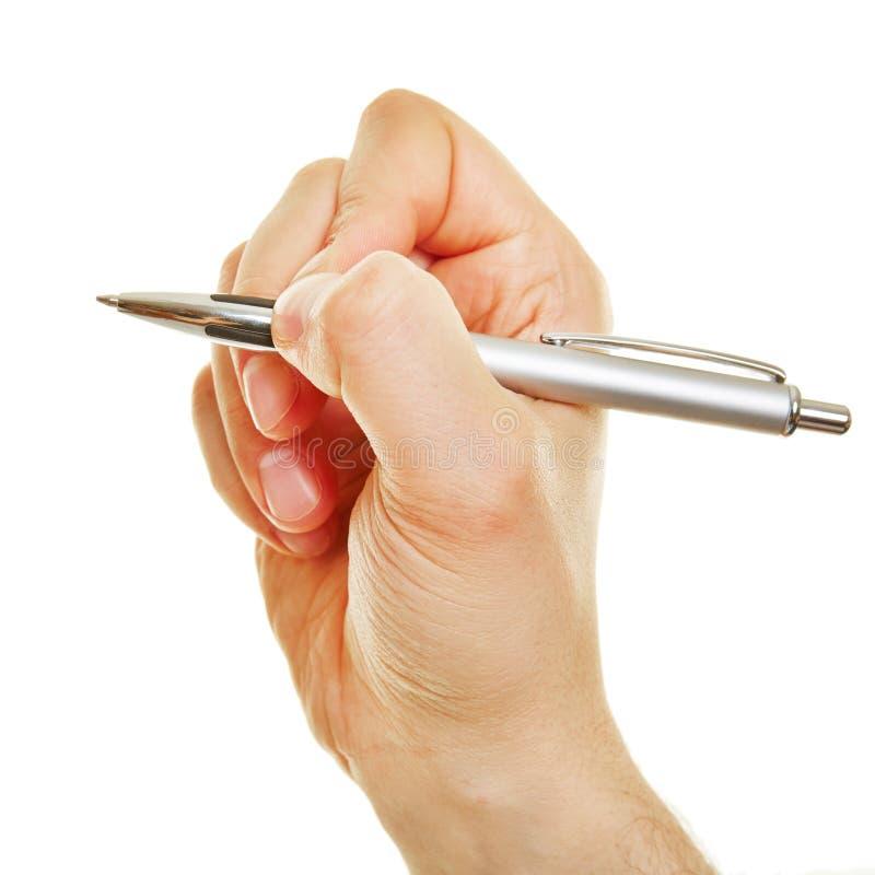 Sidosikt av den hållande pennan för hand arkivfoton