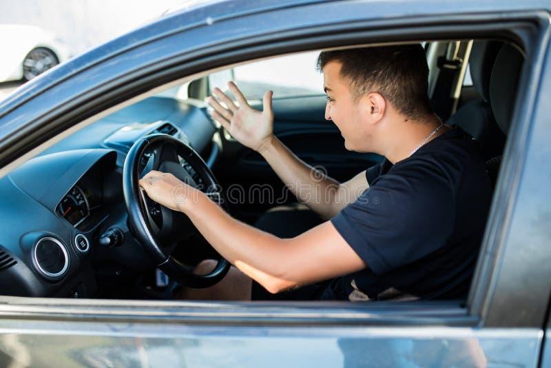 Sidosikt av den ilskna mannen i dräkten som kör en bil och tonsignaler fotografering för bildbyråer
