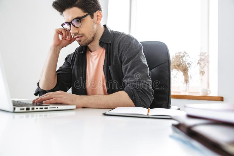 Sidosikt av den koncentrerade mannen i glasögon genom att använda bärbar datordatoren arkivbild