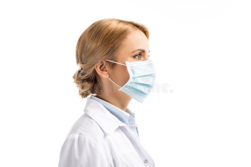 sidosikt av den kvinnlig mitt åldrades doktorn i den medicinska maskeringen som bort ser royaltyfria foton