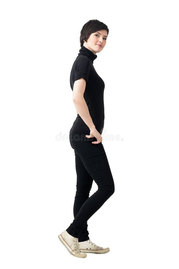 Sidosikt av den kvinnliga unga flickan i svart halvpolokrage och flåsanden med händer på höfter fotografering för bildbyråer