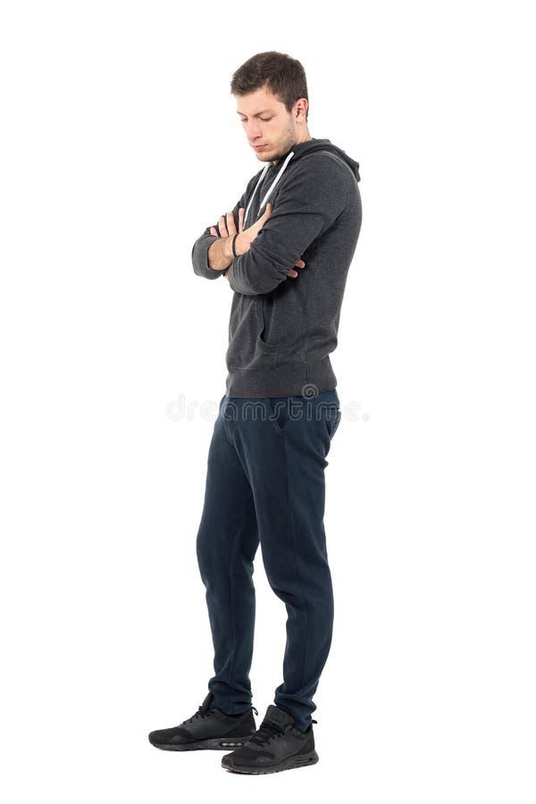 Sidosikt av den ledsna unga mannen i sportive kläder som ner ser med korsade armar royaltyfri fotografi