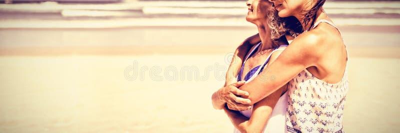 Sidosikt av den lyckliga kvinnan som omfamnar hennes moder på stranden fotografering för bildbyråer