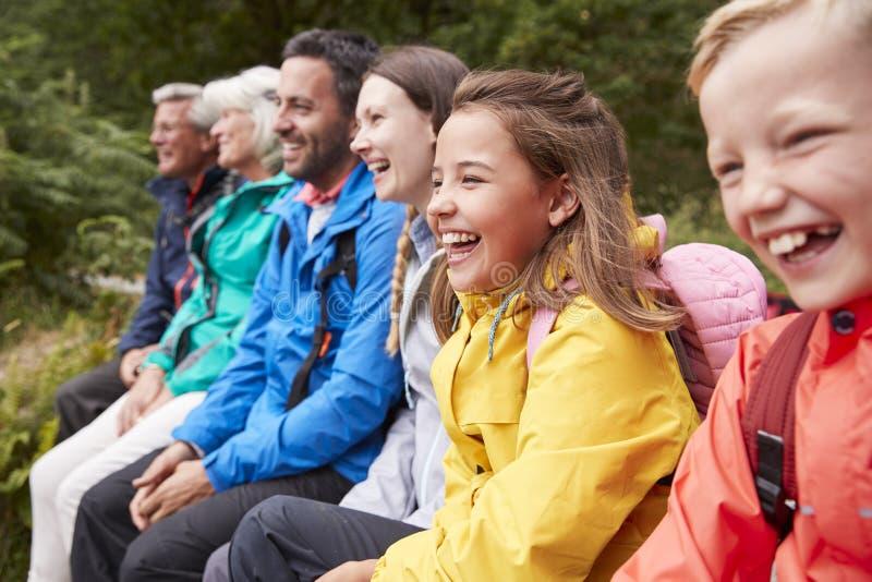Sidosikt av den mång- utvecklingsfamiljen som beundrar sikten som tillsammans sitter på kusten av en sjö som skrattar, selektiv f royaltyfria bilder