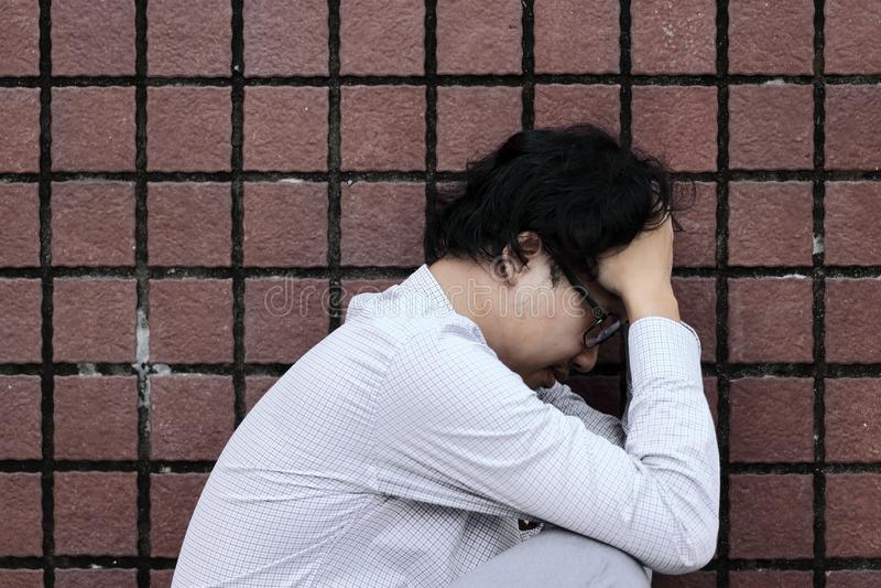 Sidosikt av den olyckliga deprimerade unga asiatiska mannen som sitter och känner sig dålig royaltyfri bild