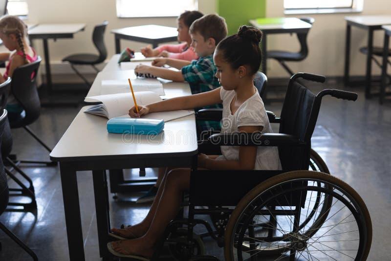Sidosikt av den rörelsehindrade skolflickan med klasskompisar som studerar och sitter på skrivbordet i klassrum fotografering för bildbyråer