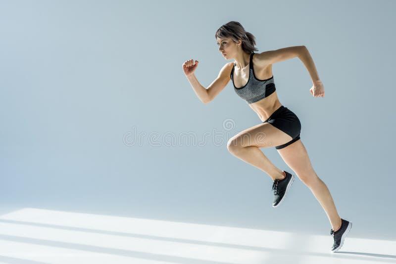 Sidosikt av den rinnande kvinnan i sportive kläder royaltyfria bilder