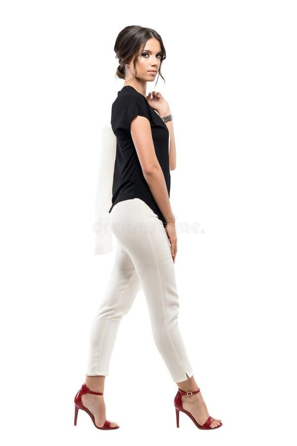 Sidosikt av den säkra ursnygga affärskvinnan i dräkt som går och ser kameran royaltyfri fotografi