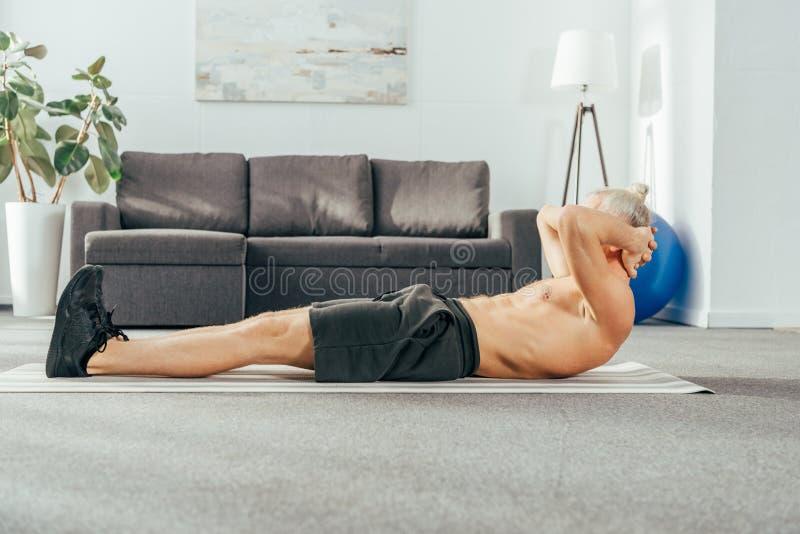 sidosikt av den shirtless mannen som gör abs för att öva på matt yoga fotografering för bildbyråer