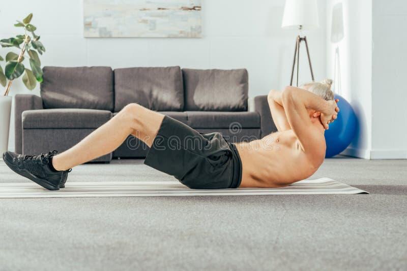 sidosikt av den shirtless vuxna mannen som gör abs för att öva på matt yoga royaltyfria foton