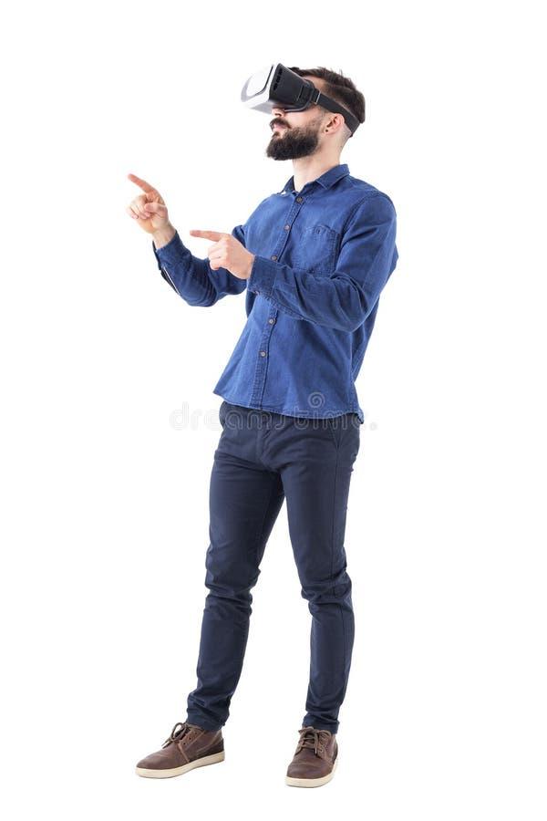 Sidosikt av den skäggiga affärsmannen som gestikulerar med handen och fingret som har virtuell verkligheterfarenhet arkivbild