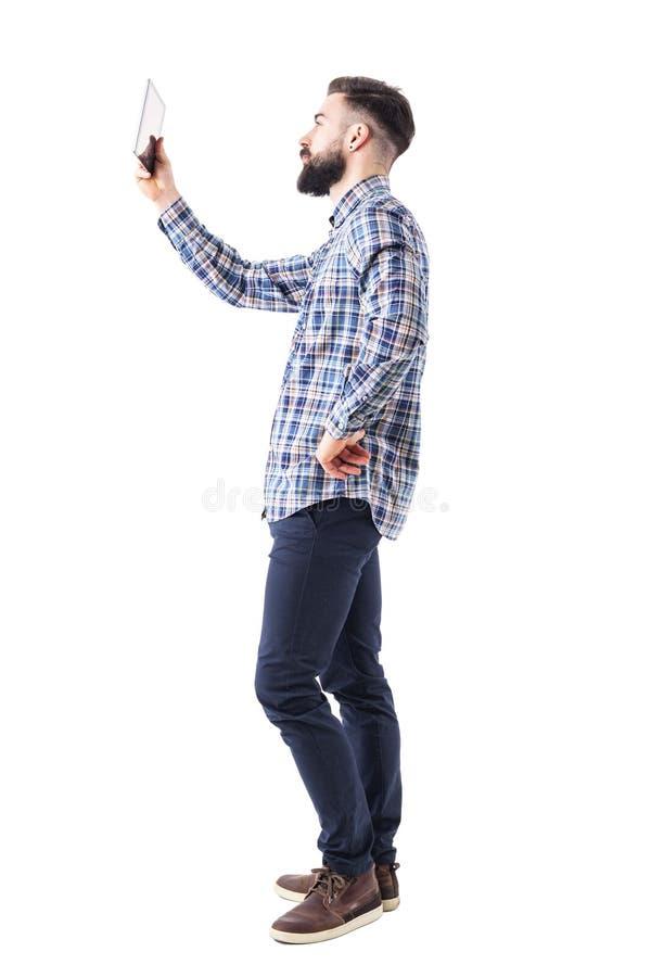 Sidosikt av den skäggiga unga datoren för minnestavla för block för affärsman hållande övre fotografering för bildbyråer