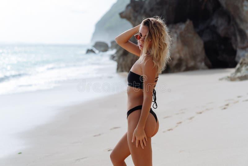 Sidosikt av den slanka sexiga modellen som poserar i baddräkt- och solglasögonbakgrund av havet på stranden på den soliga dagen royaltyfri bild