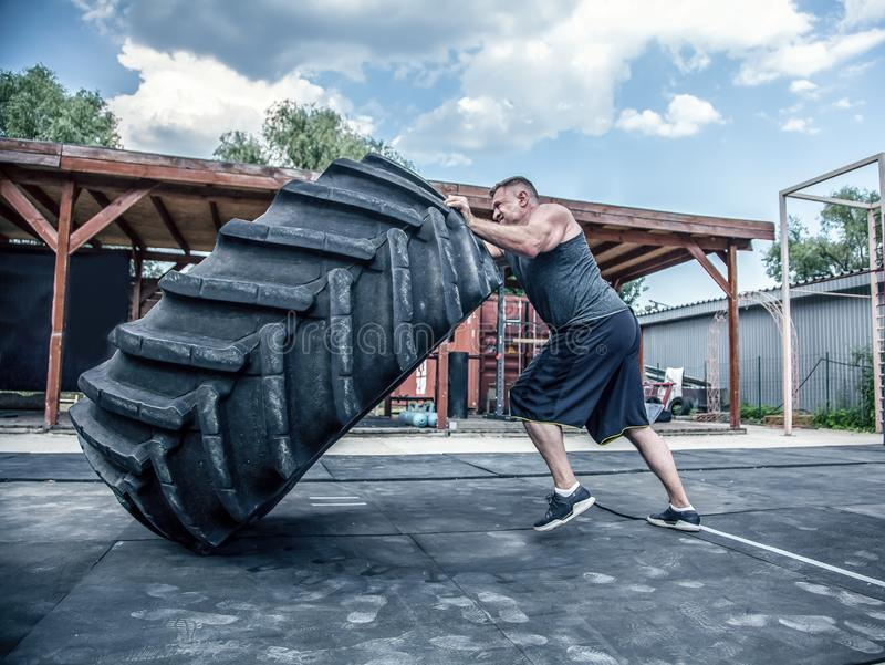 Sidosikt av den starka muskulösa konditionmannen som flyttar det stora gummihjulet i gataidrottshall Begrepp som lyfter, genomk?r royaltyfria bilder