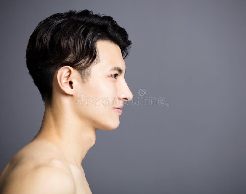 Sidosikt av den stiliga framsidan för unga män arkivbild