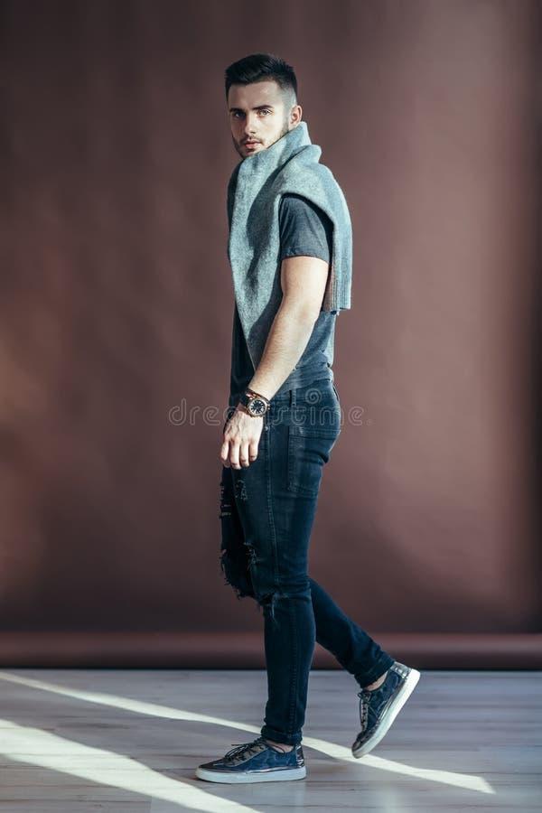 Sidosikt av den stiliga mannen som går och ser kameran arkivfoton
