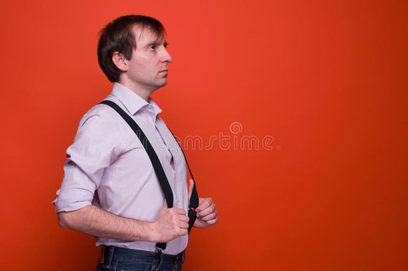 Sidosikt av den stiliga säkra mannen i rosa skjorta med händer på den svarta suspenderen som bort ser och tänker arkivbilder