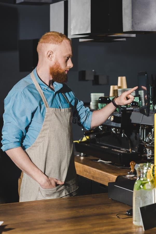 sidosikt av den stiliga unga baristaen som pekar på skärmen, medan arbeta fotografering för bildbyråer