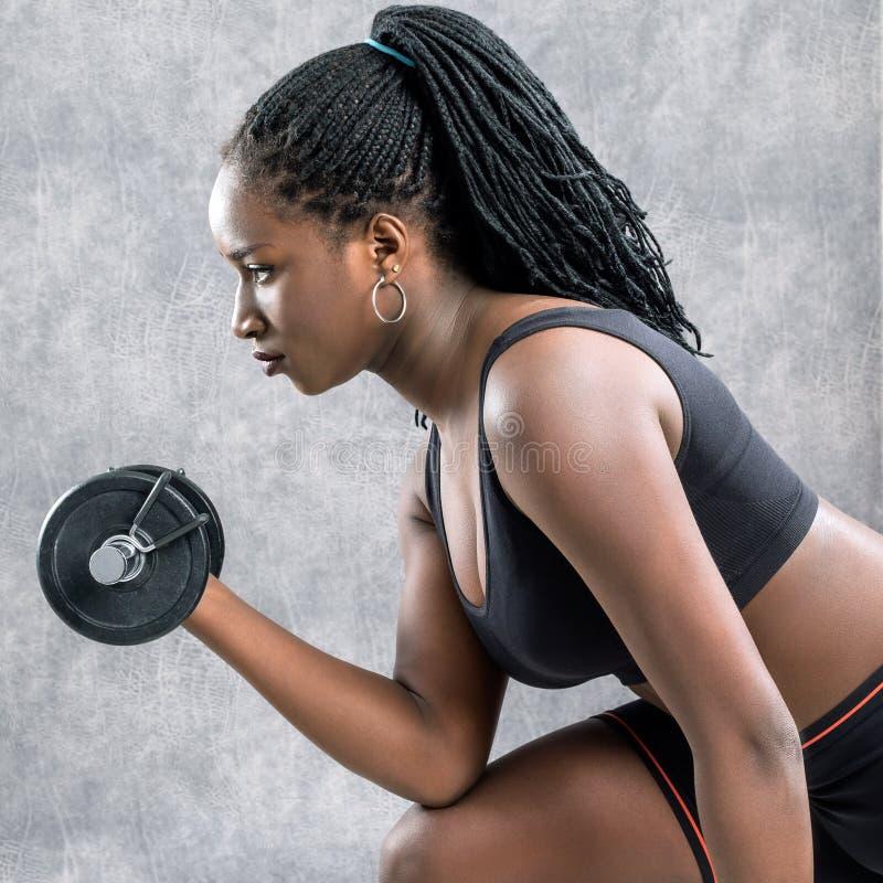 Sidosikt av den svarta tonåriga flickan som utarbetar med hanteln royaltyfri fotografi