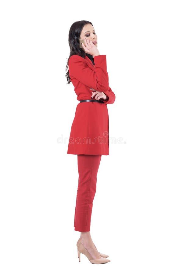 Sidosikt av den unga affärskvinnan i dräkt som talar på telefonen och ner ser arkivfoton