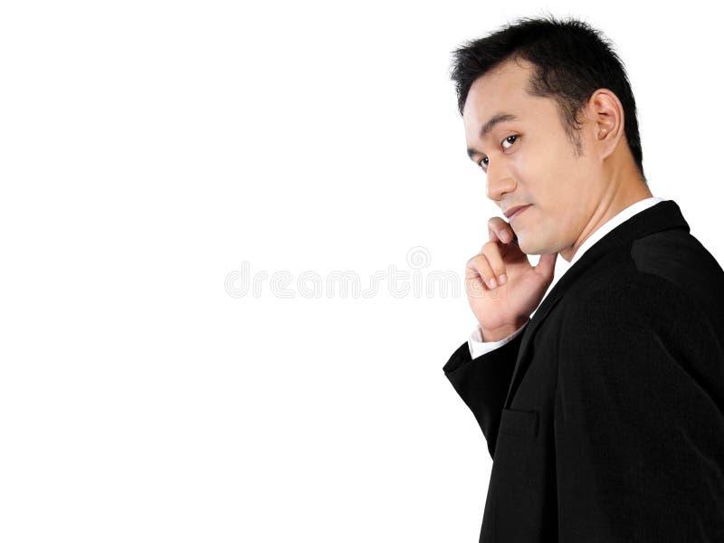 Sidosikt av den unga asiatiska affärsmannen som gör en påringning som isoleras på vit arkivbilder