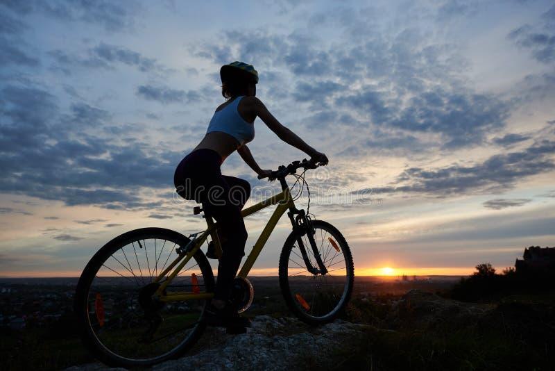 Sidosikt av den unga damen som cyklar i berg med ett aftonlandskap arkivbild