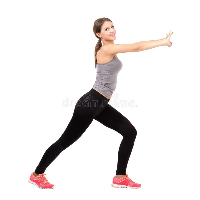 Sidosikt av den unga härliga slanka sportiga kvinnan som sträcker och övar royaltyfria foton
