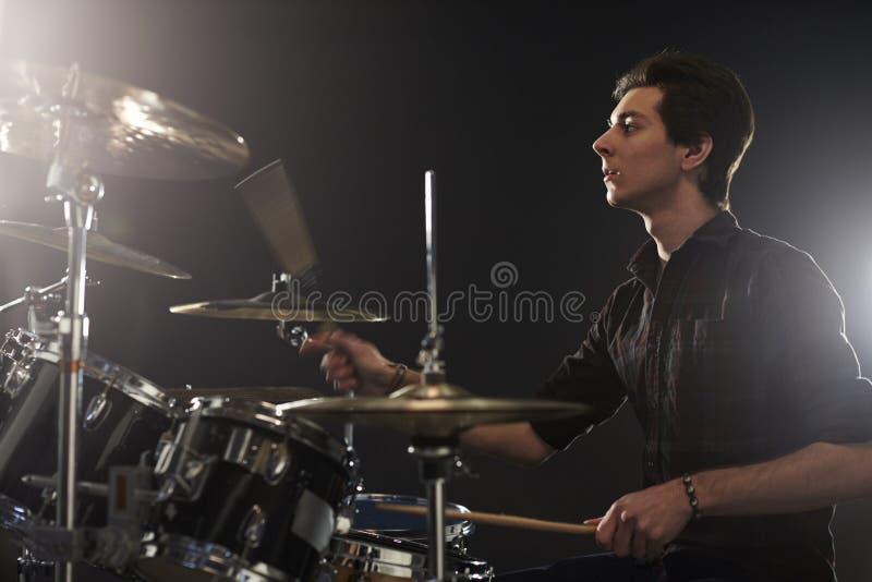 Sidosikt av den unga handelsresanden Playing Drum Kit In Studio royaltyfri foto